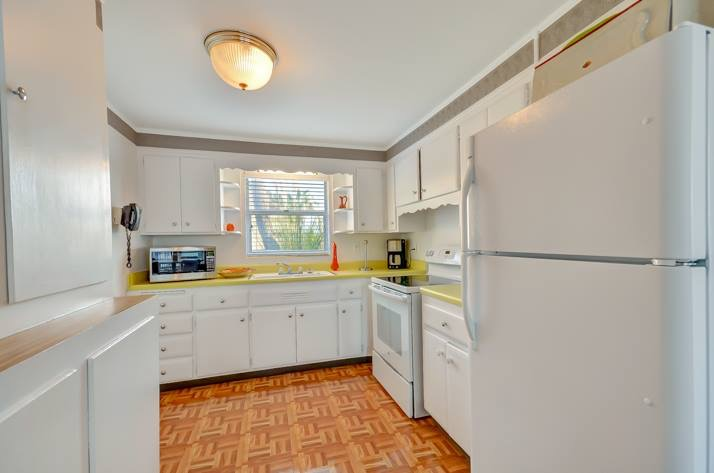 Kitchen with cabinets, refrigerator, oven, toaster and coffee maker. Window over sink.
