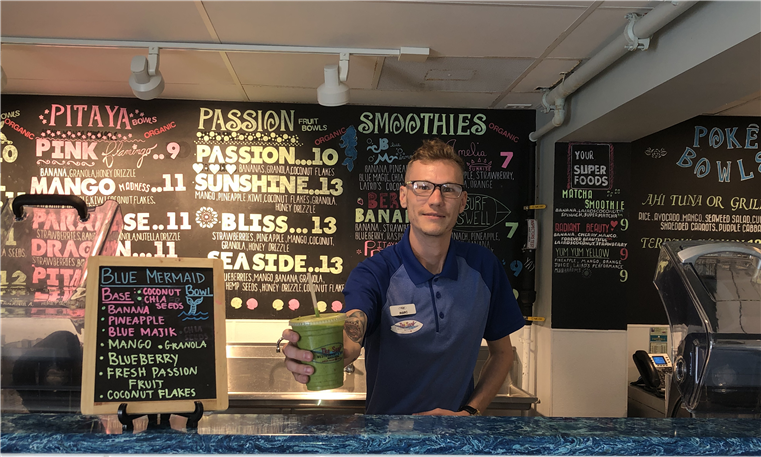 young male staff member behind smoothie bar holding out drink