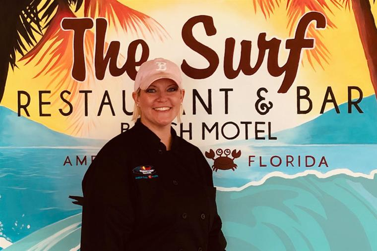 Headshot of Erin in front of The Surf sign - Cook
