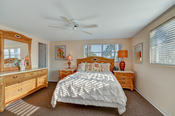Queen size bed with comforter and a wood wicker furniture set with dresser, big mirror and bedside tables with lamps