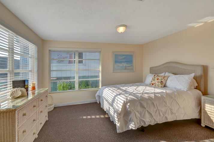 King size bed with comforters and pillows, with view of window and natural light, wicker furniture set