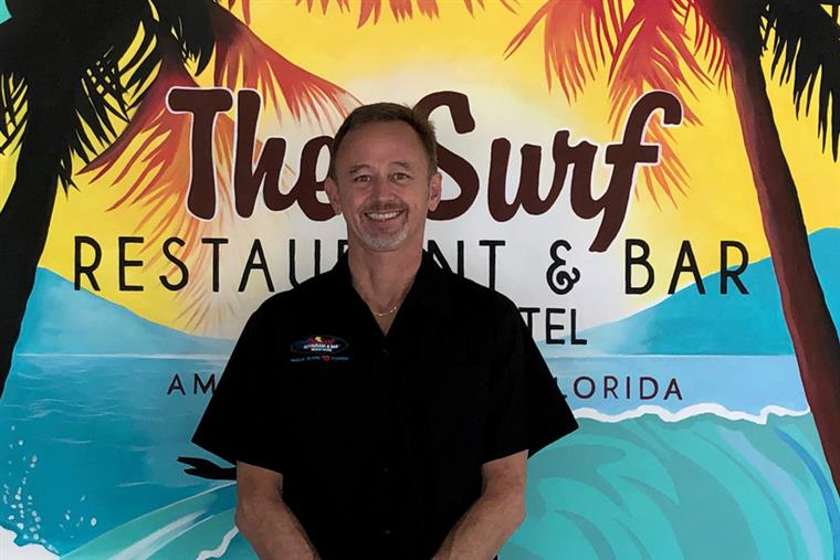 Headshot of JR - the senior front of house manager in front of the surf sign