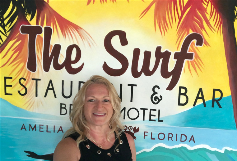 Headshot of Jodi - general manager. standing in front of The Surf sign