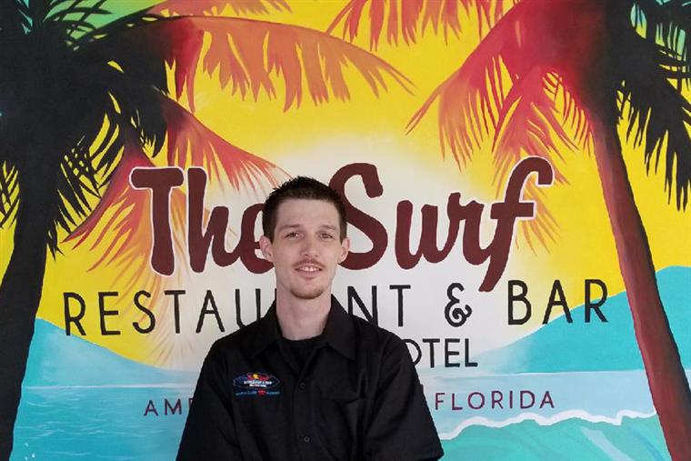 Headshot of Lance - Front of House Manager in front of the surf sign