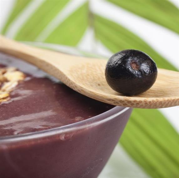 bowl of blended acai with a wooden spoon holding a whole acai berry with a leaf in the background