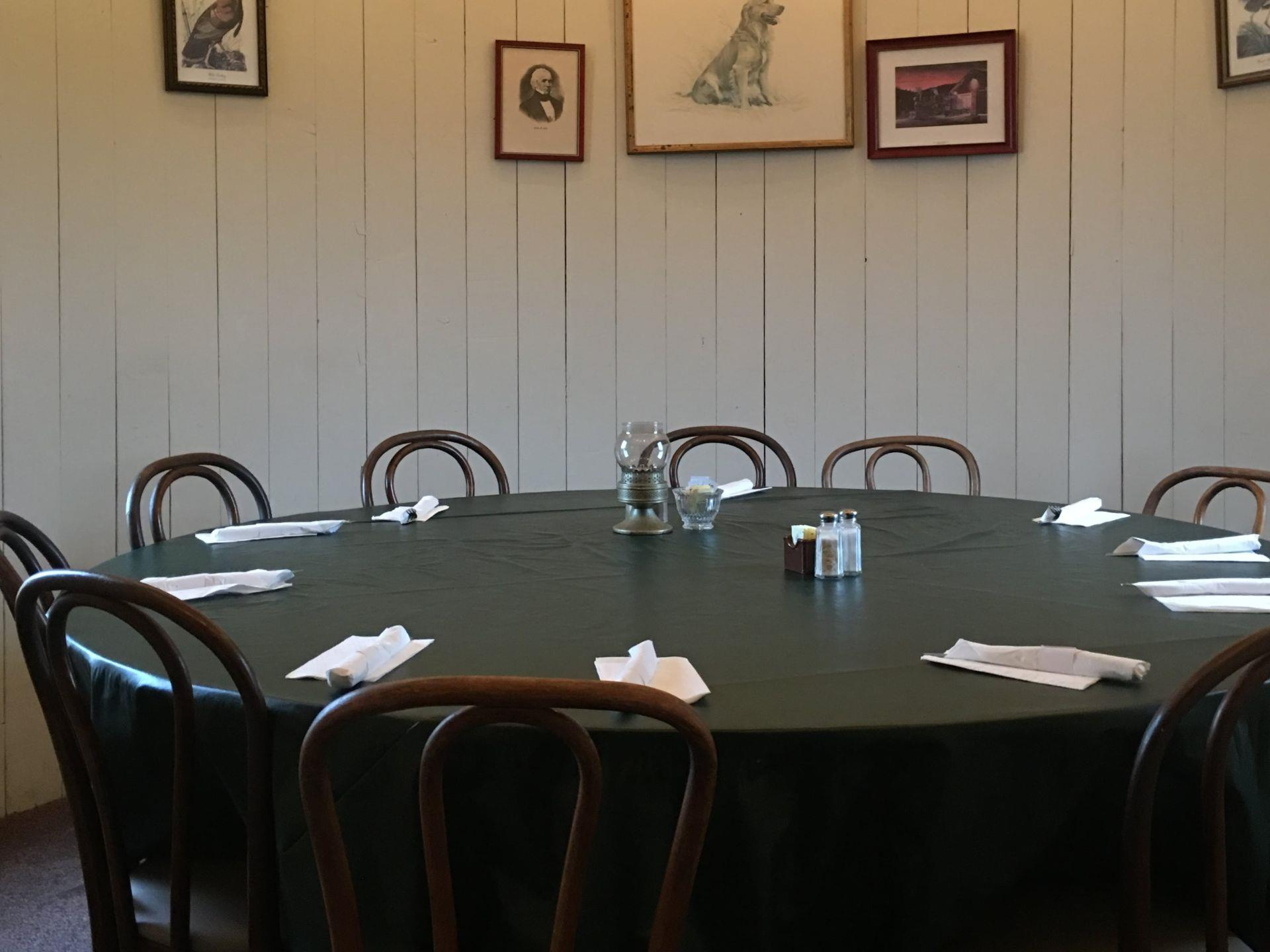 Round dining table set up with place-settings and chairs and pictures hanging on the wall