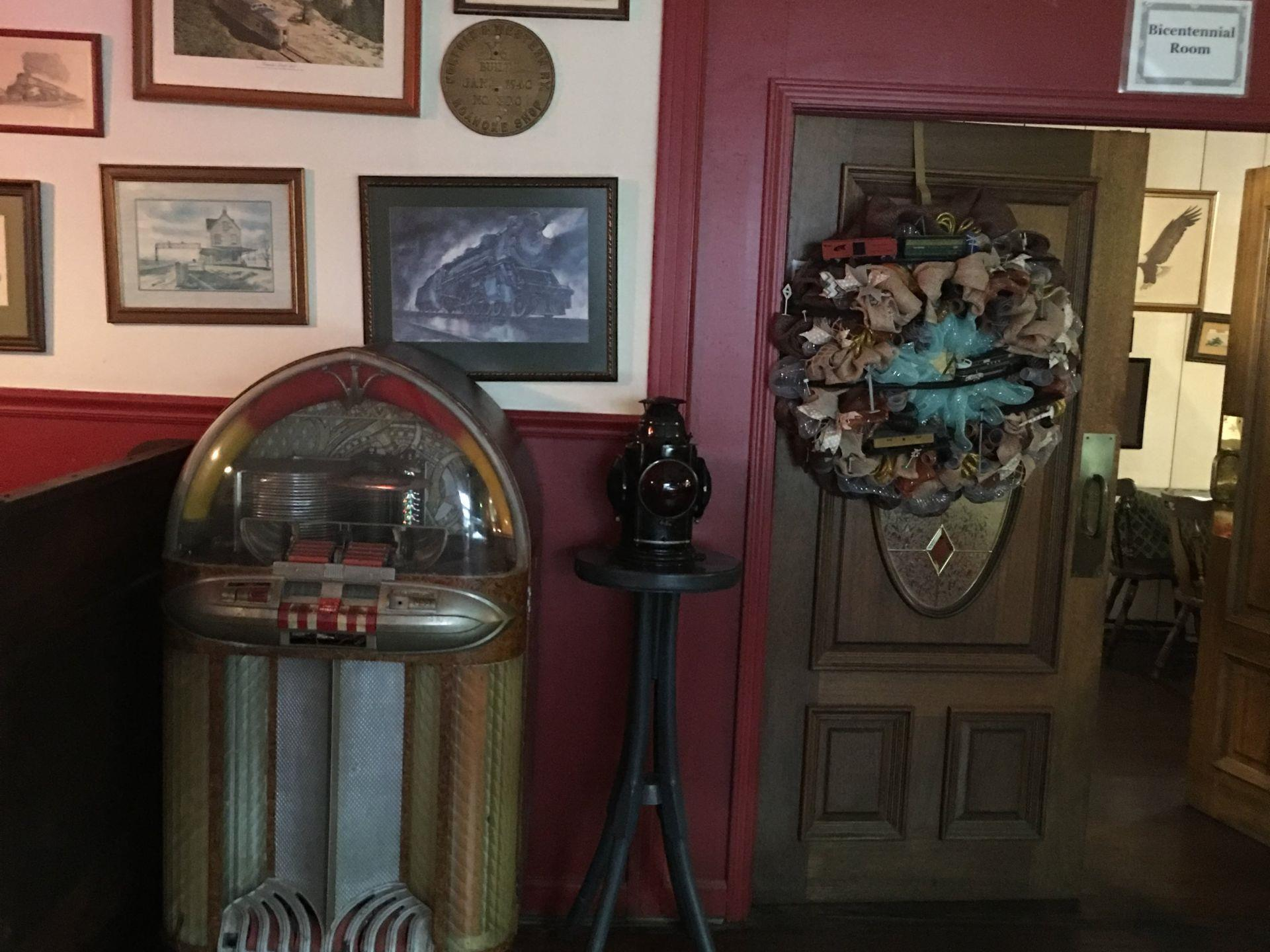 Old style jukebox in front of a wall with pictures hanging on the wall