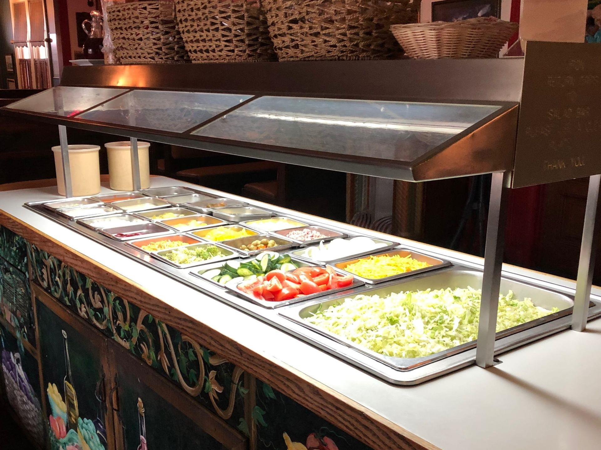 Salad bar setup with assorted toppings in containers