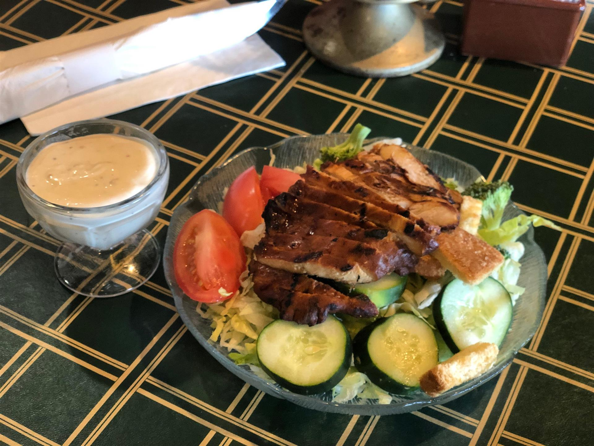 House salad topped with grilled chicken. Dressing on the side.