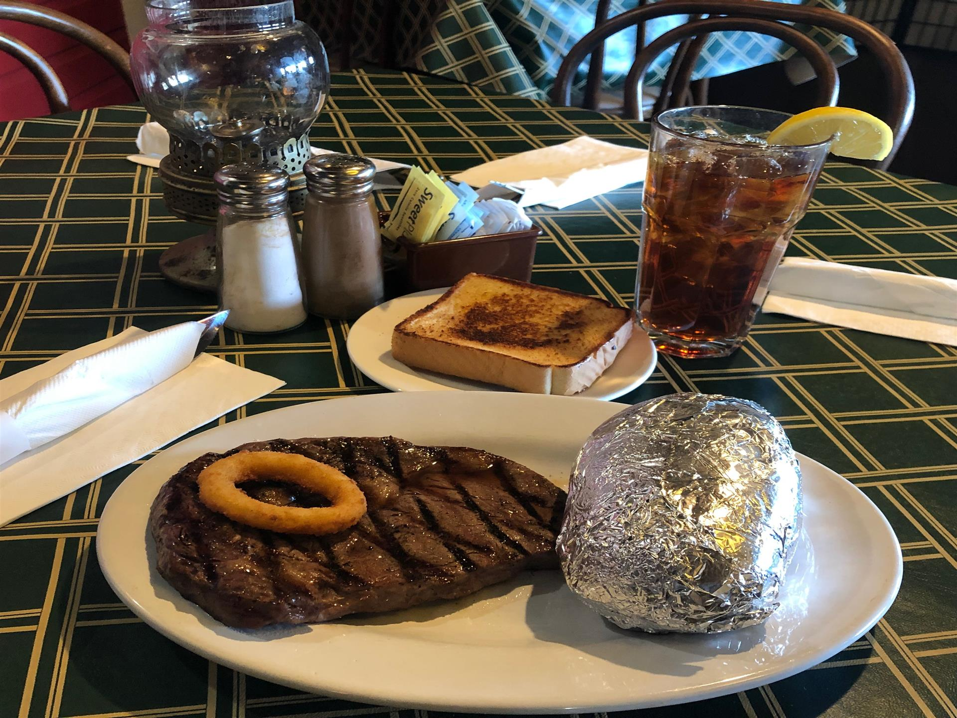 Grilled Steak on a plate with a fried onion ring on top. Baked potato on the side wrapped in foil. Toast and soda behind it.
