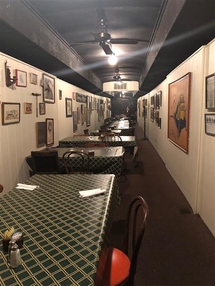 One of the dining cars at Clarksville Station. Vintage feel with White walls and a black ceiling. Mirror wall in the very back of the room. Old paintings on the wall of the trains.