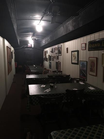 One of the dining cars at Clarksville Station. Vintage feel with White walls and a black ceiling. Old paintings on the wall of the trains.