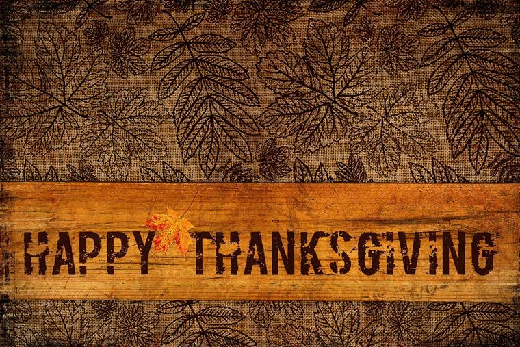 Brown background with leaf prints and a banner that says Happy Thanksgiving