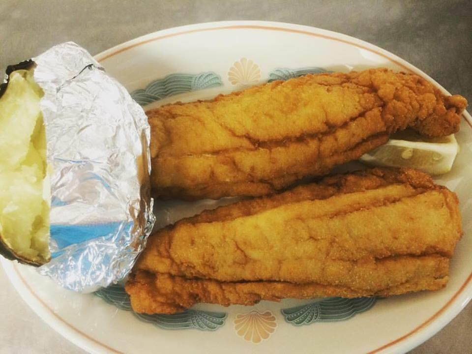 Two Fresh Local Golden Fried Flounder with a baked potato.