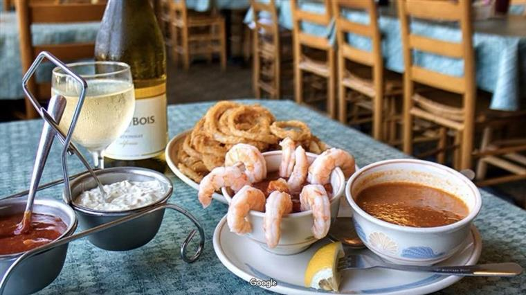 Shrimp Cocktail and Red Inlet Style Clam Chowder on a table with onion rings and a glass of white wine.