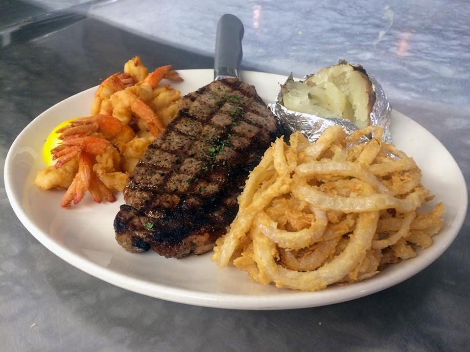 Prime Cut Angus Ribeye and Fantail Shrimp with a side of onion rings and a baked potato.