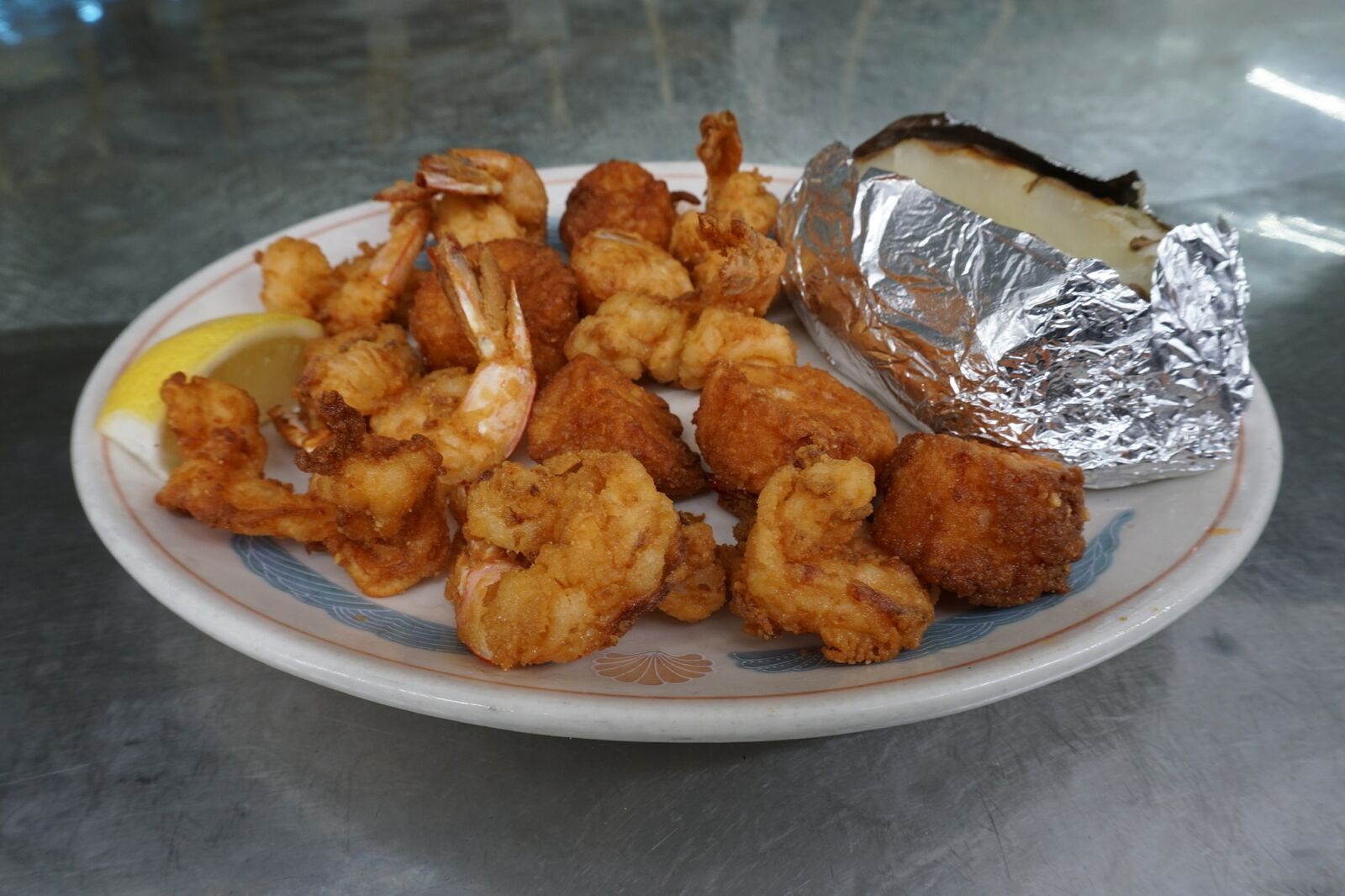 Plump and sweet sea scallops and fantail shrimp, lightly fried with a baked potato.