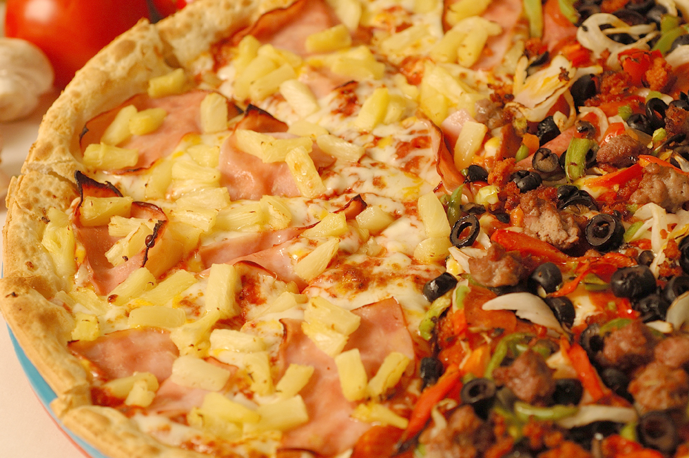 combination pizza with half ham and pineapple and half supreme with peppers, olive, onions & sausage