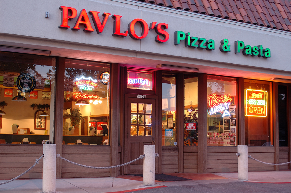 exterior shot of Pavlo's Pizza at night with sign lit up