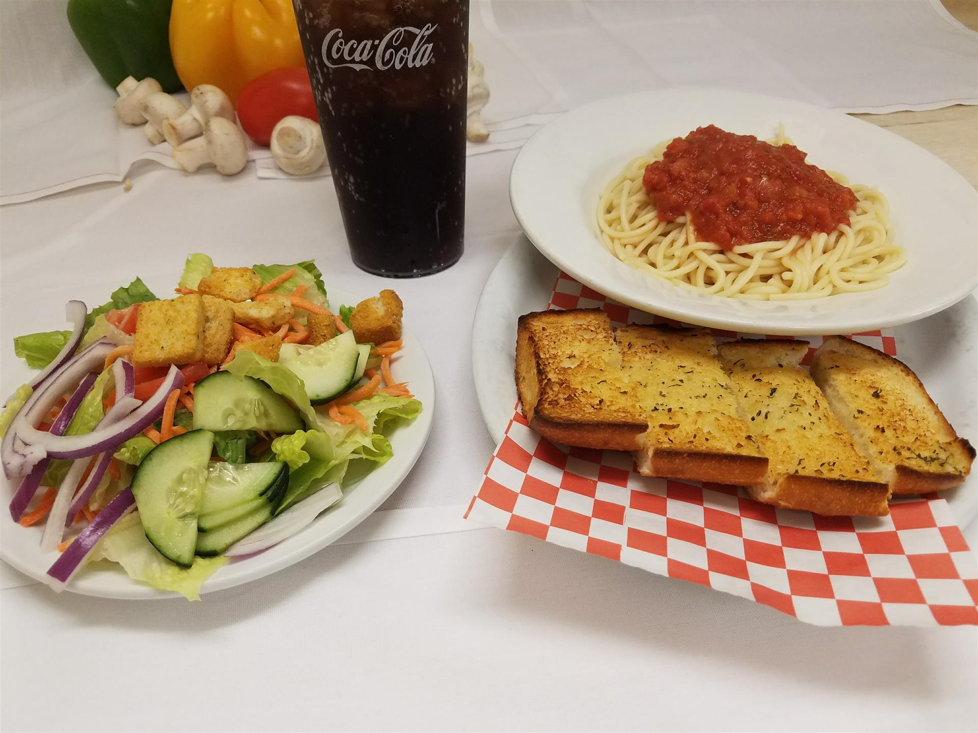 spaghetti with marinar ssuuace, house salad, and garlic bread with a soda