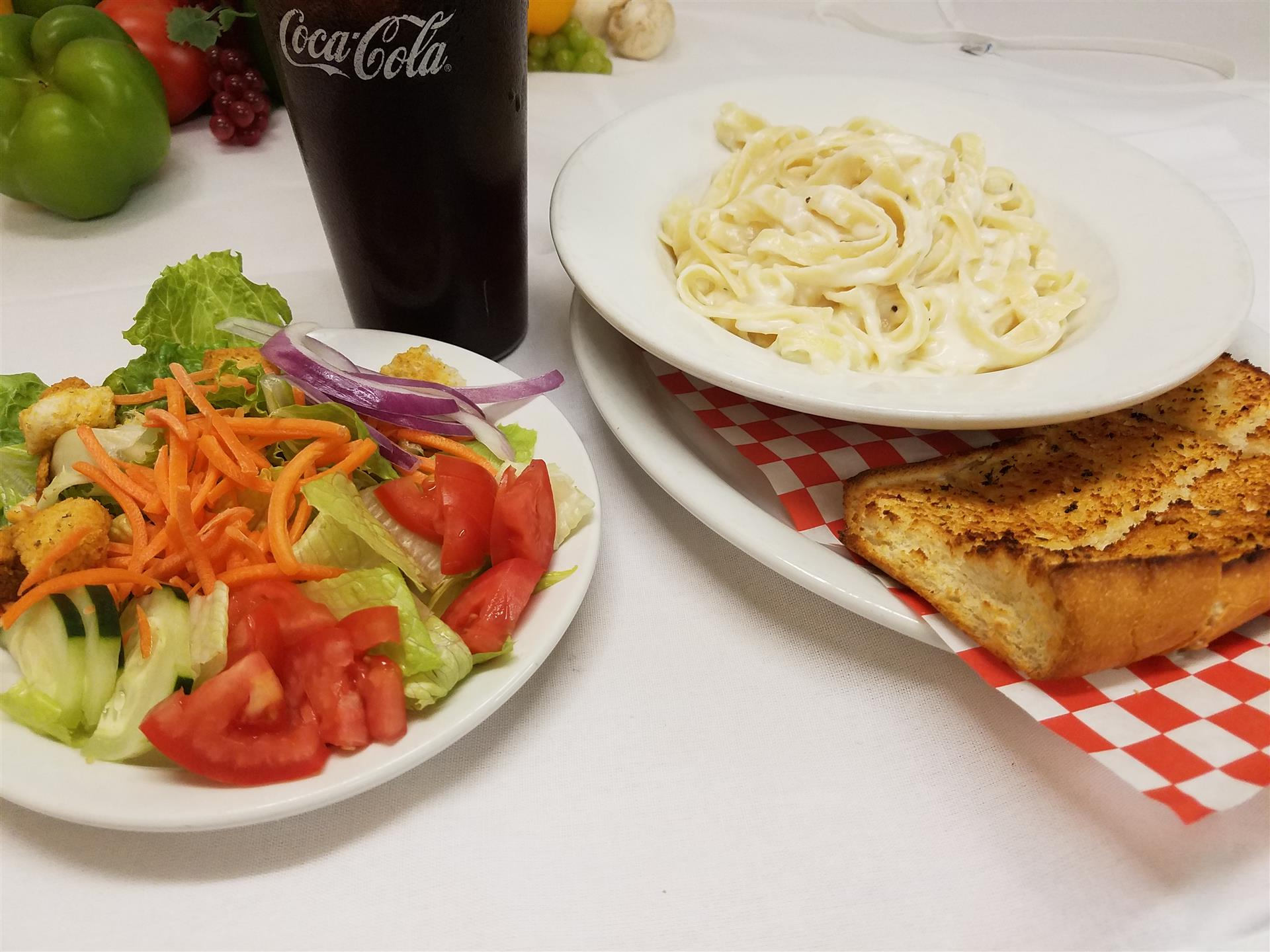 linguine alfredo with garlic bread and a house salad with a soda