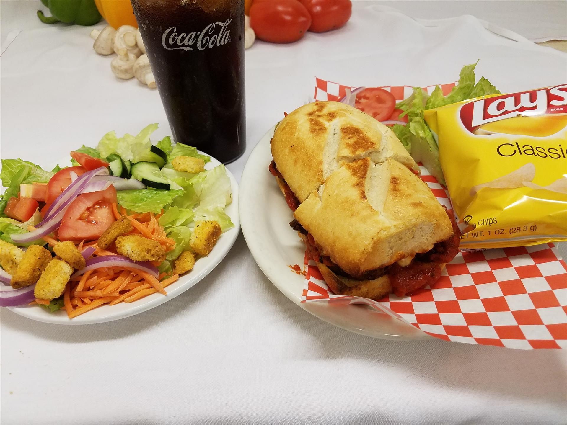 meatball sub with a house salad and a soda