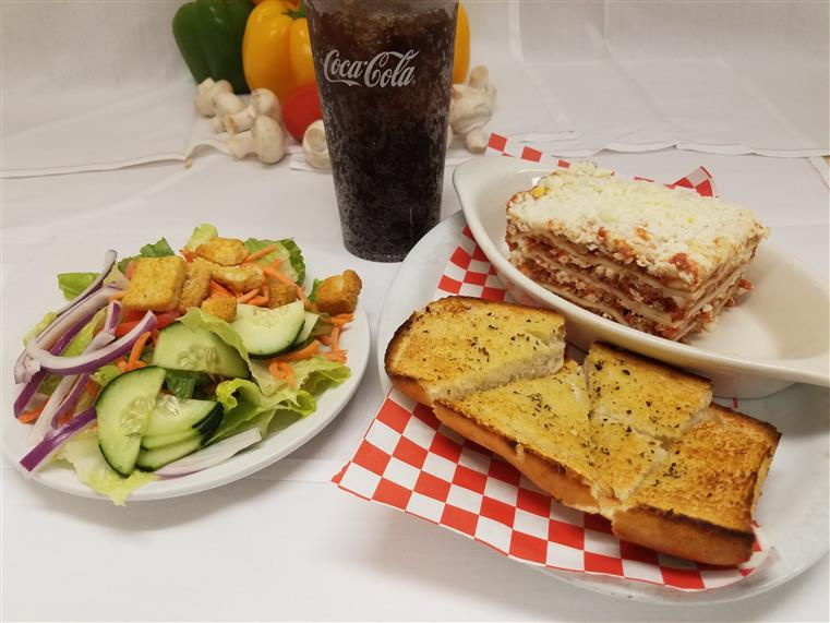 lasagna,  garlic bread, soda and a side salad