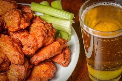 buffalo wings on plate with celery sticks and a beer in cup next to it