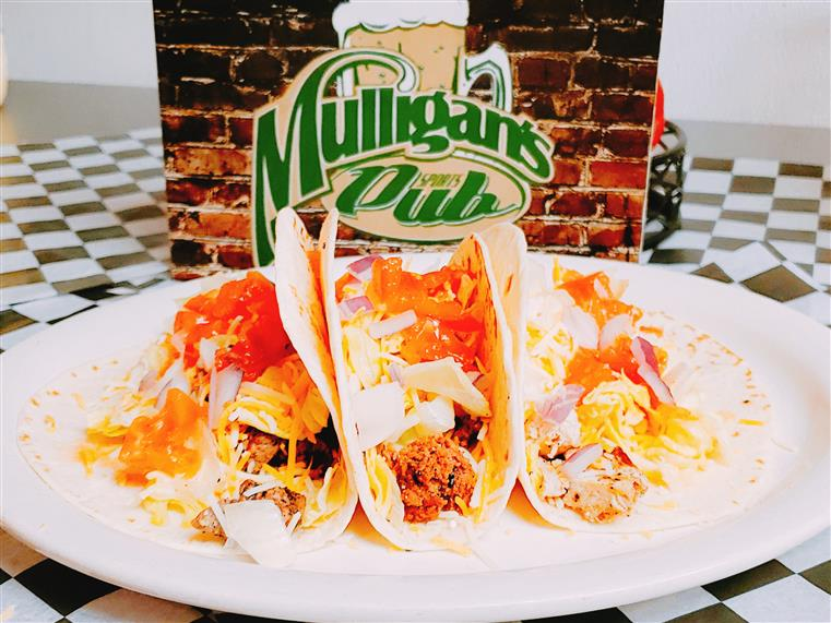 3 tacos on a white plate with mulligan's pub logo behind it
