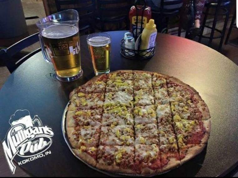Pizza cut into squares on black table next to a pitcher of beer and a glass of beer
