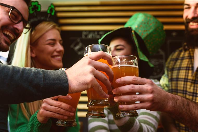 4 adults wearing irish gear cheersing with big glasses of beer