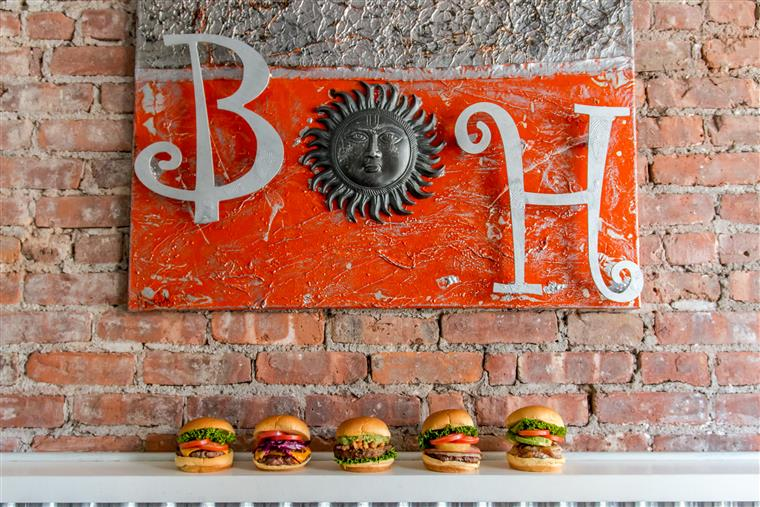 Five assorted burgers on the bar by the brick wall. Burger Heights artwork made by a local artist hanging on the wall behind.