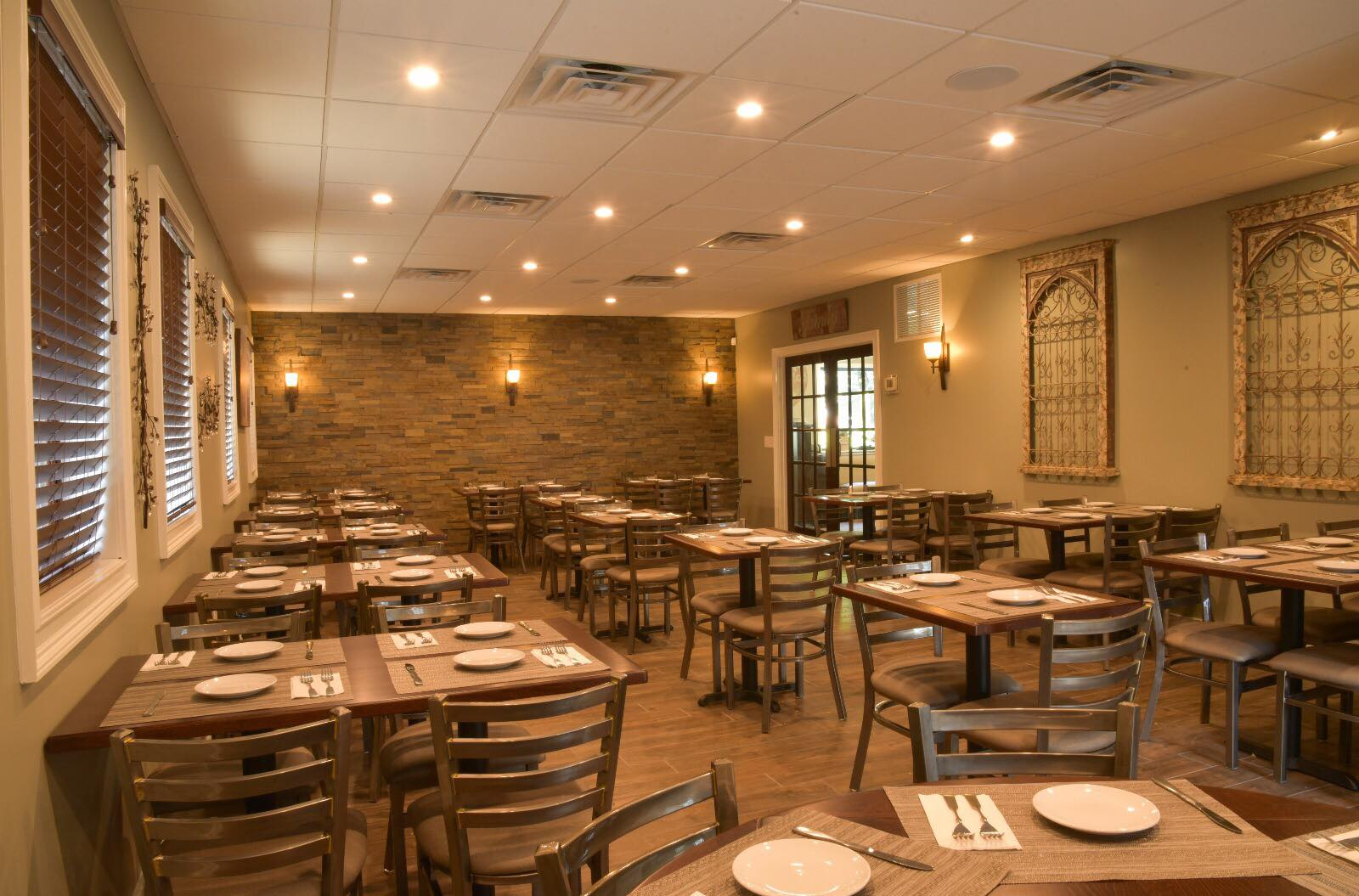 Interior of Amari's Pizzeria and Restaurant dining area with wooden tables and chairs with place settings