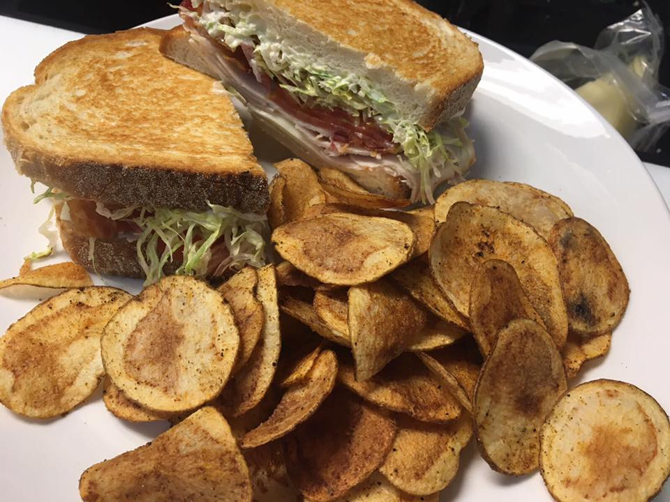 Turkey sandwich with lettuce, tomato and mayo on a plate with potato chips