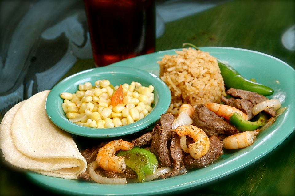 Steak and shrimp fajita plate with peppers and onions, rice, flour tortillas and a bowl of corn