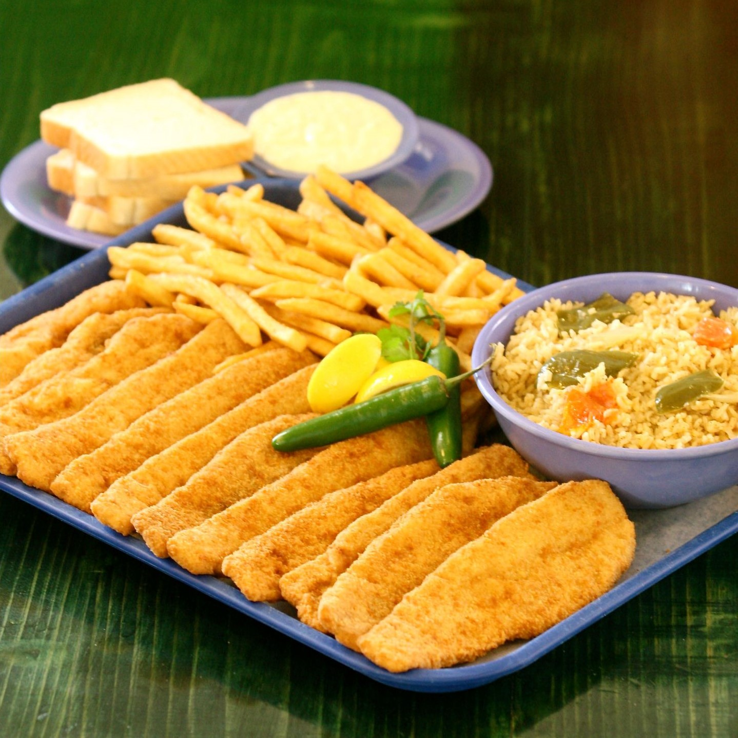 Fried fish sticks on a tray with French fries, hot peppers and a bowl of spicy rice