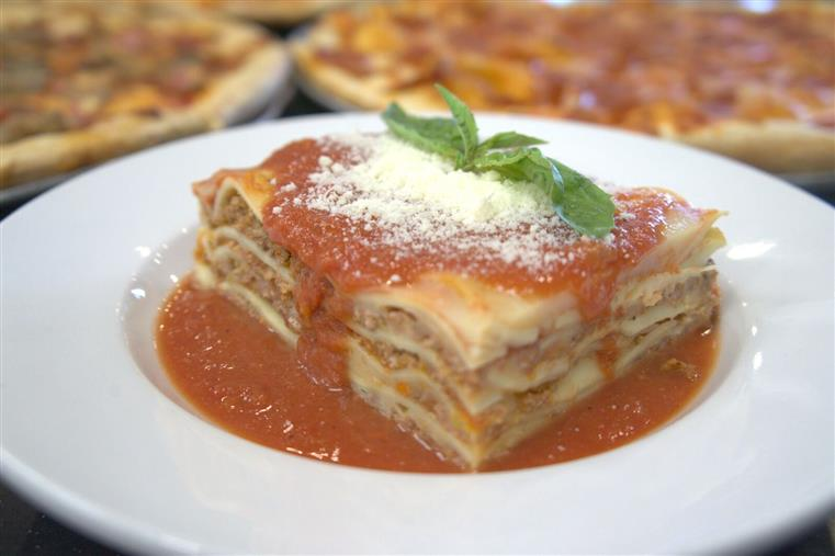 meat lasagna with sauce, topped with cheese and basil