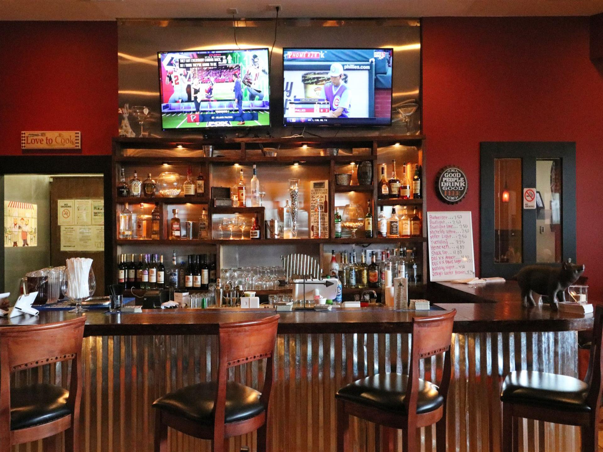 Interior bar area with chairs by a bar-top and assorted bottles on shelves behind a bar with two TVs on a wall