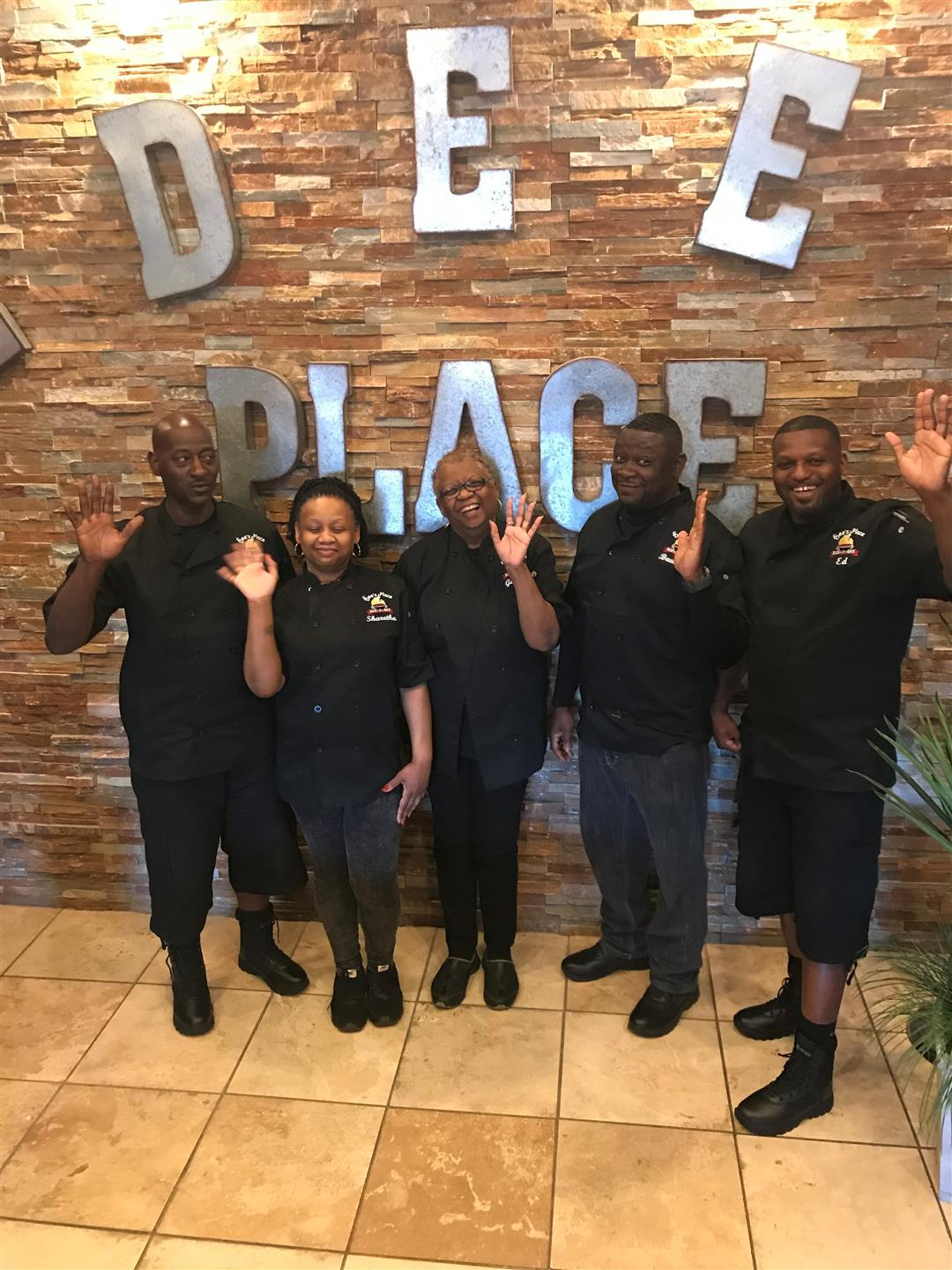 5 staff members in black edee's place uniforms waving and smiling in front of the interior brick wall that says Edee's Place