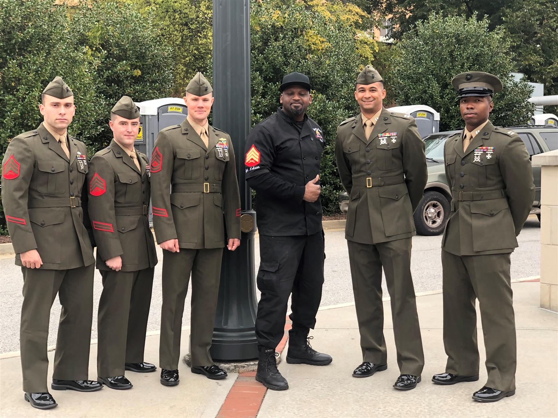5 marines in green uniforms standing with edee in his black marine uniform