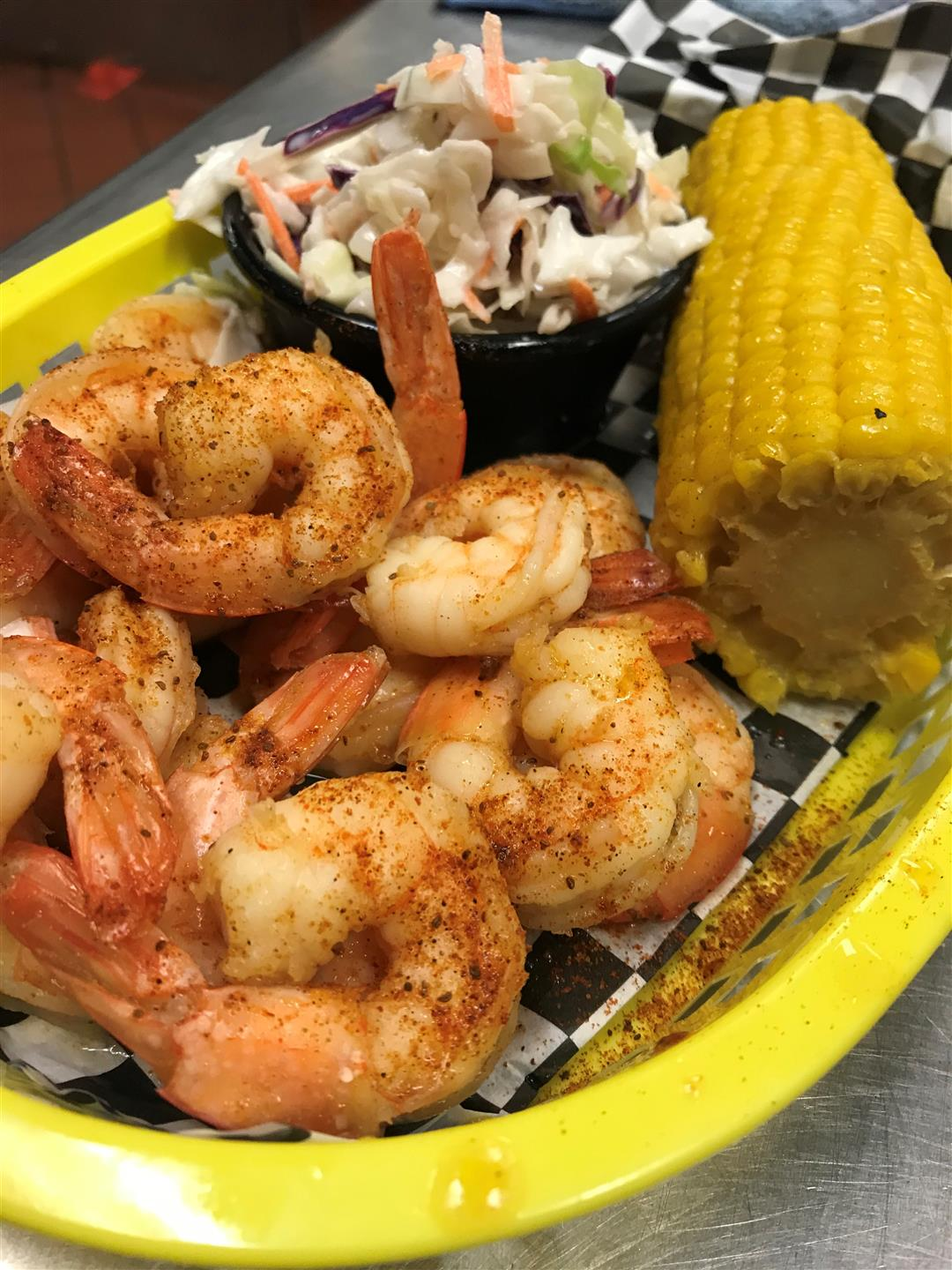 spicy boiled shrimp in a food tray with half a corn on the cob and a side of coleslaw