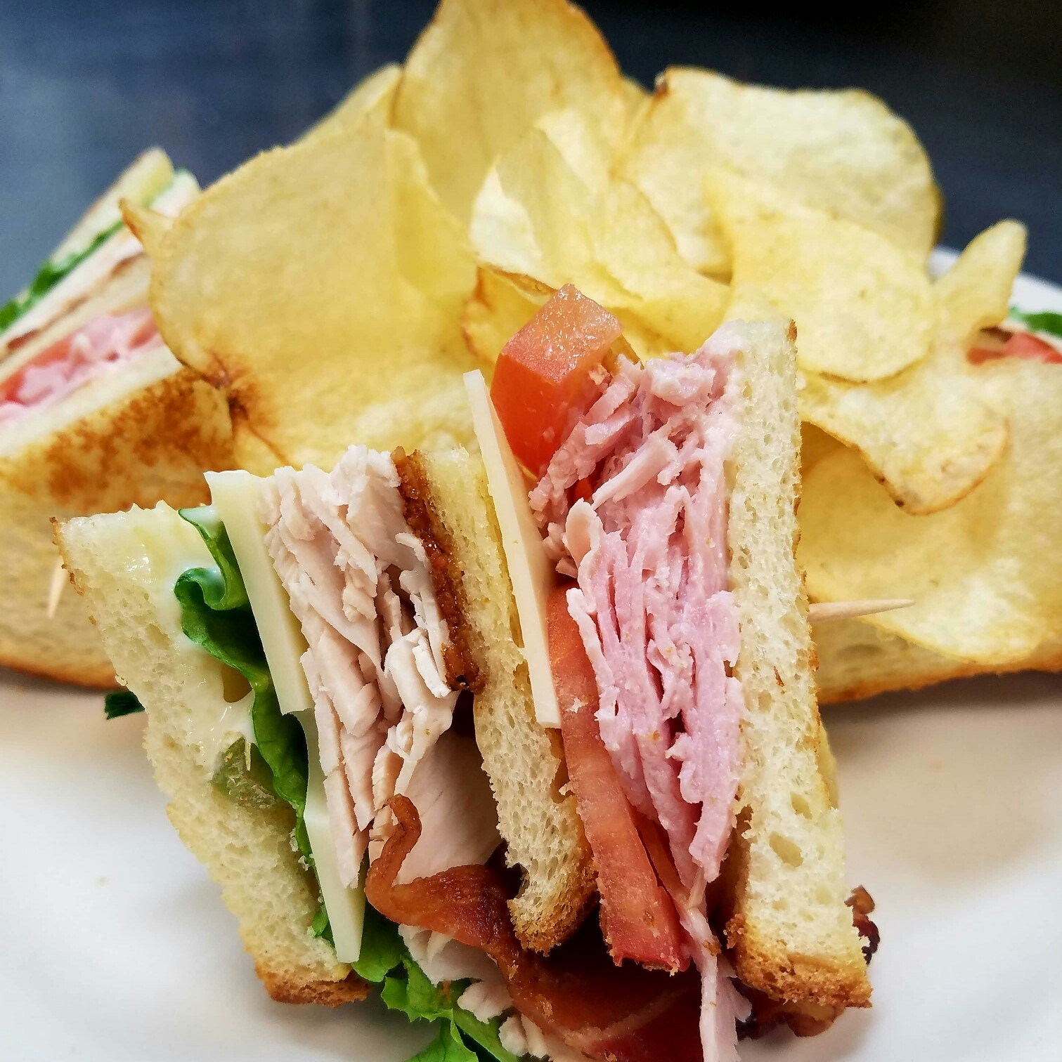Turkey and ham club sandwitch with lettuce, tomato, cheese and bacon with potato chips