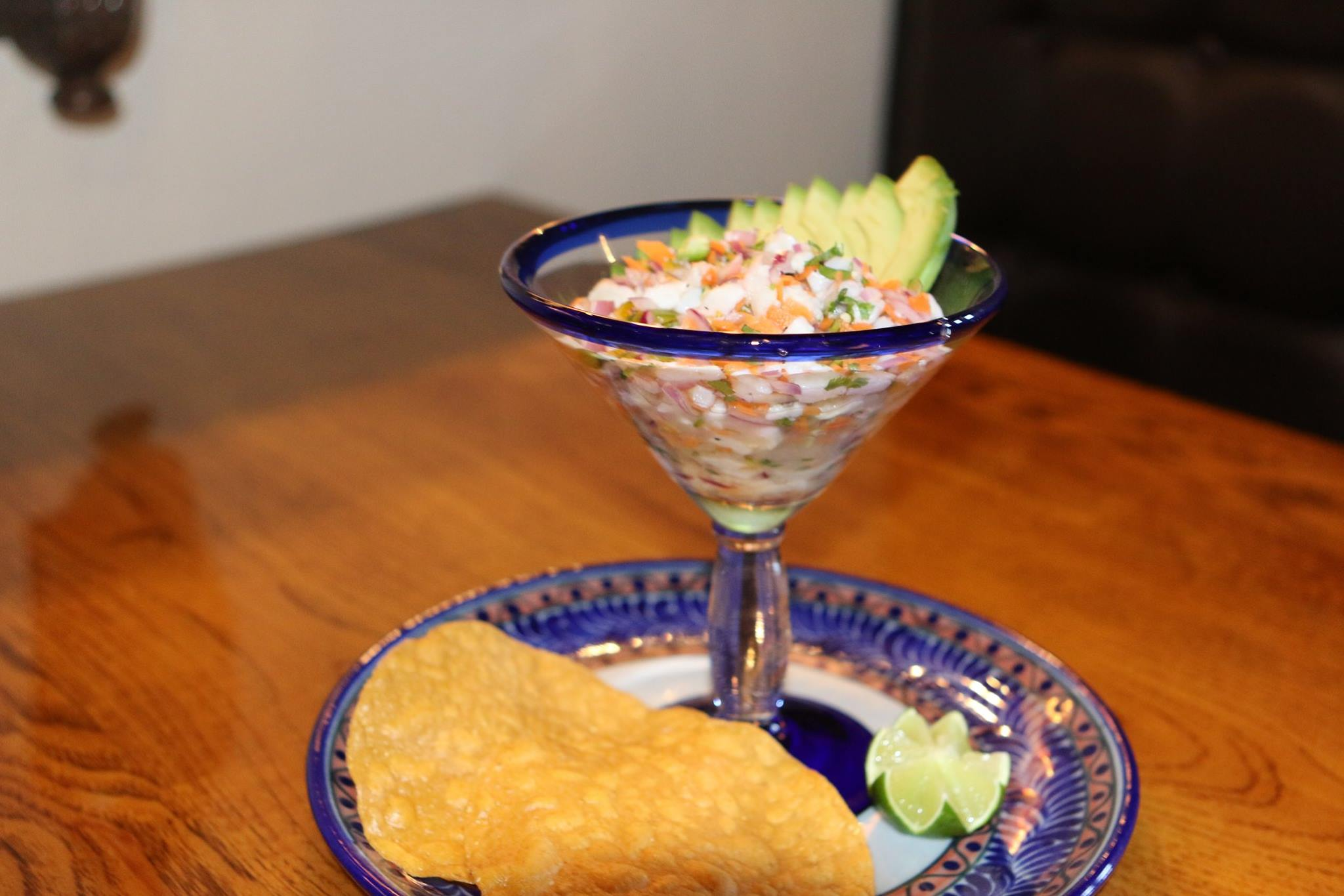 Ceviche with sliced avocado in a margarita glass served with tortilla chips and lime