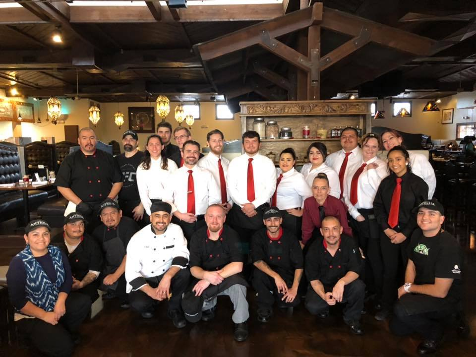 Large group of people smiling for a photo dressed in restaurant server attire
