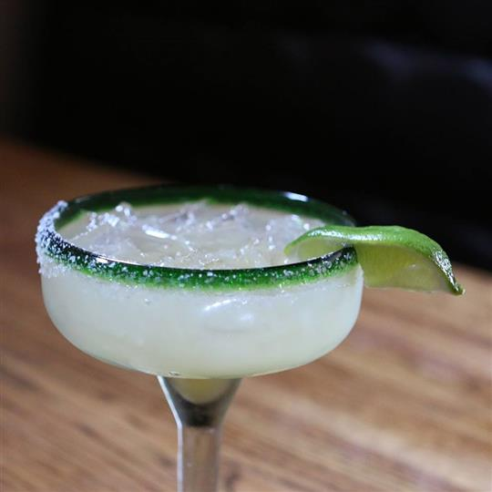 Close-up of a margarita with salted rim and a lime