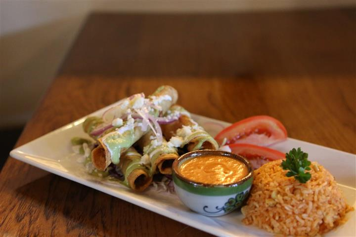 Chicken taquitos with tomatillo saice and red onion served with a bowl of dipping sauce, sliced tomatoes and yellow rice