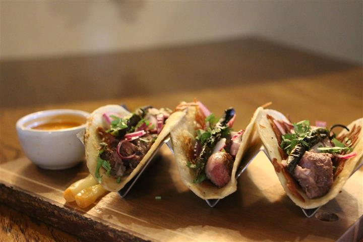 Three carnitas in soft shells with lettuce and red onion in taco holders on a wood board
