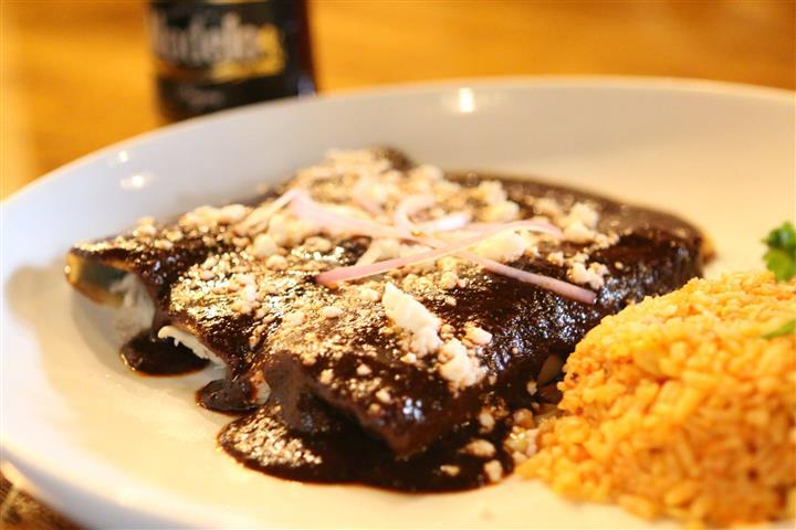 Chicken enchiladas in mole sauce topped with red onion and cheese and a side of yellow rice