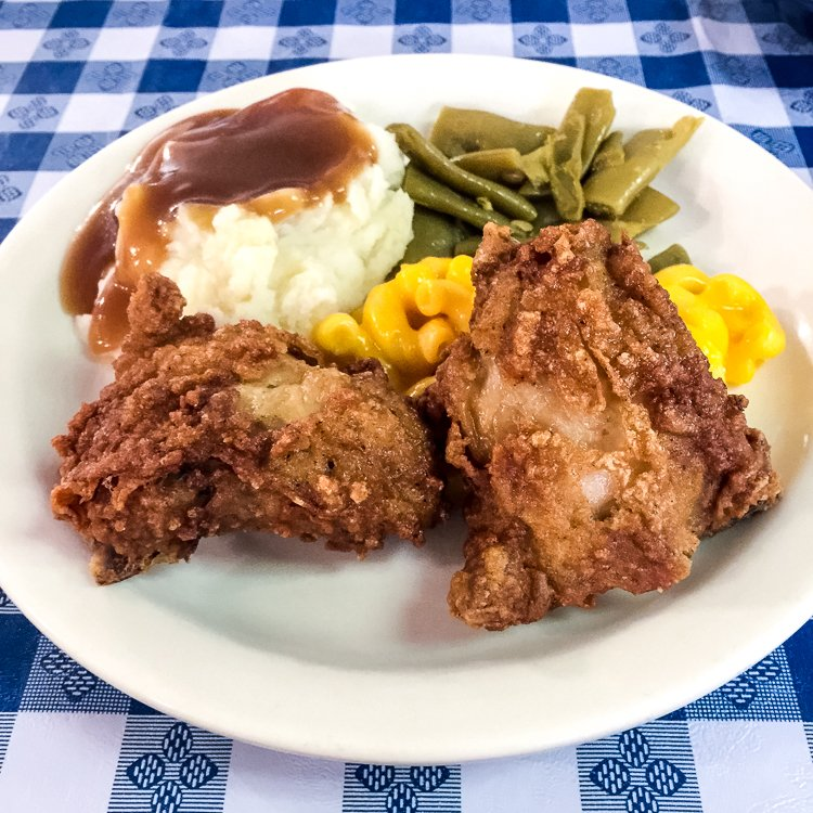 Plate of fried chicken, mashed potatoes with gravy, green beens and corn