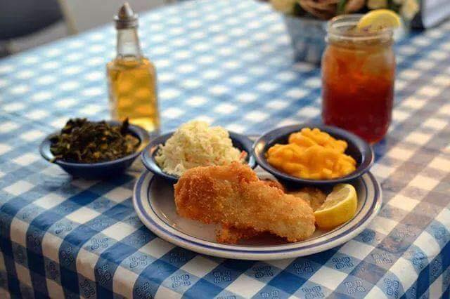 Fried chicken on a plate with mac and cheese, cole slaw and collard greens with a bottle of vinegar and a small mason jar of iced tea with lemon